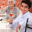Young man having dinner with his grandmother — Stock Photo
