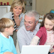 Pensioners with grandchildren using computer — Stock Photo