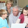 Stock Photo: Pensioners with grandchildren using computer