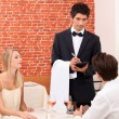 Couple being served by a waiter — Stock Photo