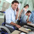 Stock Photo: Min wheelchair with mobile phone at work