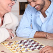 Young man playing checkers with older woman — ストック写真