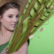 Woman in hat holding large leaves - Stock Photo