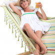 Blonde woman resting and drinking in a hammock - Stock Photo