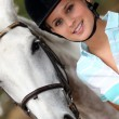 Portrait of a young woman with her horse - Stock Photo
