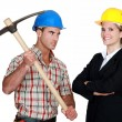 Builder aiming his pickaxe at a smiling architect — Stock Photo
