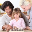Young family playing chess — Stock Photo
