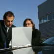 Couple with their laptop on their car — Stock Photo #9043137