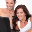 Couple in bed with laptop — Stock Photo #9043142
