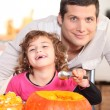 A father and his little girl laughing and eating a pumpkin — Stockfoto #9043332