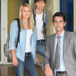 Two students and their lecturer in the corridor - Stock Photo