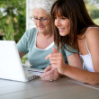 Foto Stock: Mother and daughter using laptop