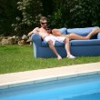 Couple relaxing on sofa by the pool - Stock Photo