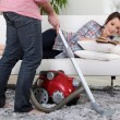 Man using vacuum cleaner — Stockfoto