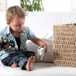 Stock Photo: Young boy playing with his toys
