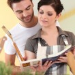 Couple cooking from recipe book — Stock Photo #9046315