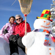Father and daughter stood with snowman — Stock Photo