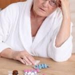 Senior woman in bathrobe about to take drugs — Stock Photo