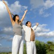 Couple stood in a field with their arms raised — Stock Photo