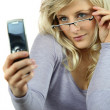 Stock Photo: Blond womlifting glasses to read text message