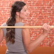 Woman exercising with a stick — Stock Photo