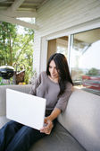 Woman using her laptop on her veranda — Stock Photo