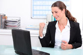 Smart woman punching the air in delight after looking at her laptop — Stock Photo