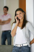 Man sulking while his girlfriend is talking on the phone — Stock Photo
