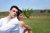 Couple sitting back to back in a field — Stock Photo