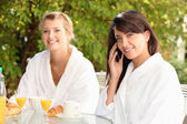 Young women having breakfast on the patio — Stock Photo