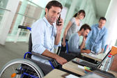 Man in wheelchair with mobile phone at work — Stok fotoğraf
