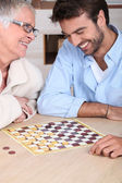 Young man playing checkers with older woman — Stock Photo