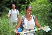 Vrouw kaart lezen tijdens het wandelen door lange gras — Stockfoto