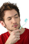 Young man looking at his toothbrush — Stock Photo