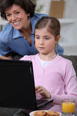 Little girl using laptop at home — Stock Photo