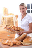 Young woman working in a bakery — Stock Photo