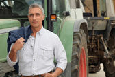 Farmer posing in front of his tractor — Stock Photo