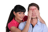 Woman covering a man's eyes — Stock Photo