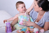Mother with young baby and bottle on bed — Stock Photo