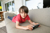 Little boy laying on sofa with hand-held video game — Stock Photo