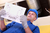 Man looking at plans for a heating installation — Stock Photo