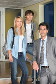 Two students and their lecturer in the corridor — Stock Photo