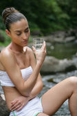 Woman drinking glass of water by the river — Stock Photo