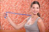 Mujer utilizando un extensor de brazo — Foto de Stock
