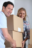 Couple moving a pile of large cardboard boxes — Stock Photo