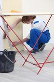 Woman putting up wallpaper — Stock Photo
