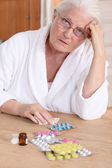 Senior woman in bathrobe about to take drugs — Stock Photo