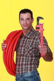 Handwerker halten, ein Engländer und ein Rohr-Schlauch — Stockfoto