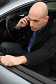 Man on phone getting out of his car — Stock Photo