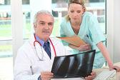 Medico esaminando una radiografia con il suo assistente — Foto Stock